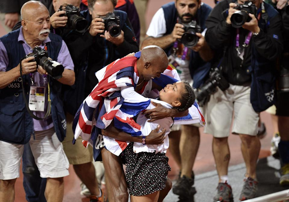 Britain's Mo Farah, center left, embraces his daughter Rihanna after he won gold in the men's 10,000-meter final during the athletics in the Olympic Stadium at the 2012 Summer Olympics, London, Saturday, Aug. 4, 2012. (AP Photo/Martin Meissner)