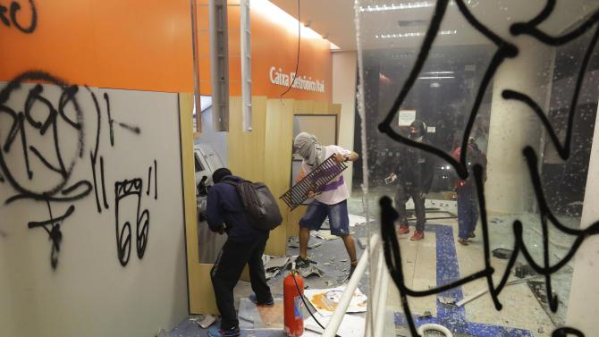 Protestors destroy ATM machines at a local a bank in Sao Paulo, Brazil, Tuesday, June 18, 2013. Thousands of demonstrators flooded into a square in Brazil's economic hub, Sao Paulo, on Tuesday. Sparked earlier this month by a 10-cent hike in bus and subway fares and organized via social media, the nationwide protests are giving voice to growing discontent over the gap between Brazil's high tax burden and the low quality of public infrastructure, echoing similar mobilizations in Turkey, Greece and other parts of the globe where weariness with governments has exploded in the streets. (AP Photo/Nelson Antoine)