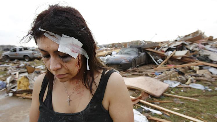 Cindy Wilson texts to friends Monday, May 20, 2013 after her home was destroyed by a massive tornado that ripped through Moore, Okla., in the afternoon. Wilson and her husband, Staff Sgt. B. Wilson, took cover in their bathtub when the tornado hit. Cindy received a deep gash to her forehead and her wound was treated by first responders at the scene. (AP Photo/ The Oklahoman, Jim Beckel)