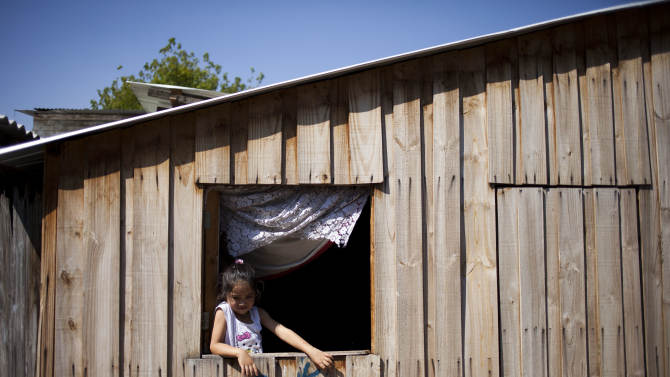 "A girl looks out from a house at the San Pablo shanty town in Santiago, Chile, Wednesday, Jan. 23, 2013.  European, Latin American and Caribbean leaders gathering for this weekend's economic summit will likely see only one side of Chile _ the polished, upscale country where tourists and investors stay in five-star hotels in a sparklingly clean financial district nicknamed ""Sanhattan,"" well away from Santiago's slums. (AP Photo/Victor R. Caivano)"