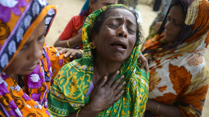 """A woman grieves as the body of a relative was brought to the morgue after it was pulled out from the rubble of a garment factory building that collapsed last week in Savar, near Dhaka, Bangladesh, Saturday, May 5, 2013. The death toll in the factory building collapse in Bangladesh rose to more than 530 on Saturday, a day after the country's finance minister downplayed the impact of the disaster on the garment industry, saying he didn't think it was """"really serious."""" (AP Photo/Ismail Ferdous)"""