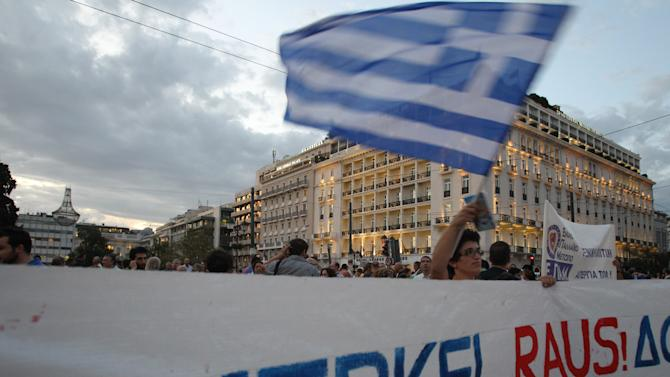 """A protestor waves a Greek flag in Athens on Monday, Oct. 8, 2012 during an union anti-austerity rally a day before the visit by German Chancellor Angela Merkel. The authorities are keen to prevent embarrassing riots. More than 7,000 police will be on security duty in the capital from early Tuesday, while public gatherings will be banned in much of the city center and on a 100-meter (yard) radius from the route her motorcade will follow. The ban will not affect the main protests, but will prevent demonstrators from reaching the German embassy, where a populist right wing party was planning a protest. Banner says """"Merkel leave""""(AP Photo/Thanassis Stavrakis)"""