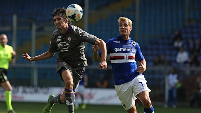 Fiorentina defender Stefan Savic, left, heads the ball past Sampdoria forward Maxi Lopez during a Serie A soccer match between Sampdoria and Fiorentina, in Genoa, Italy, Sunday, March 30, 2014