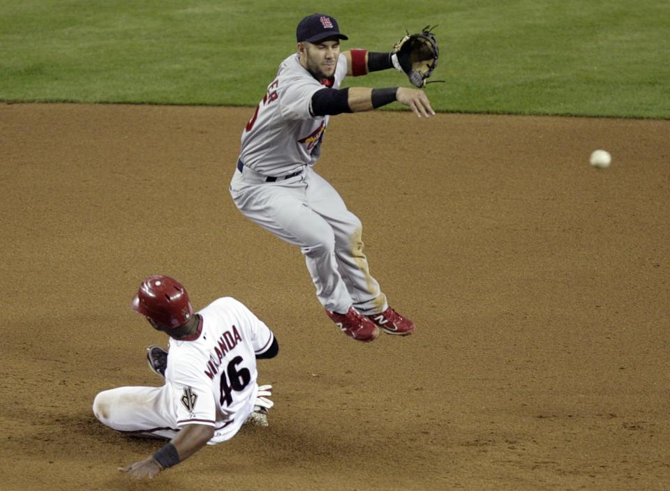 St. Louis Cardinals second baseman Skip Schumaker, top, leaps to avoid the slide by Arizona Diamondbacks' Juan Miranda, bottom, as he throws to first to turn a double play on a ball hit by Barry Enright in the fourth inning of a baseball game Monday, April 11, 2011, in Phoenix. (AP Photo/Paul Connors)