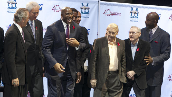 ORRECTS THAT BUSS WAS 80-YEARS-OLD, AND NOT 79 AS ORIGINALLY SENT -  FILE - In this Nov. 7, 2011 file photo, Los Angeles Lakers owner Jerry Buss, third from right, looks towards Magic Johnson, third from left, during a ceremony of the Magic Johnson Foundation in Los Angeles. Also shown are former Lakers team members Pat Riley, left, Mitch Kupchak, second from left, Bill Sharman, second from right, and James Worthy, right. Buss, the Lakers' playboy owner who shepherded the NBA franchise to 10 championships, has died. He was 80. Bob Steiner, an assistant to Buss, confirmed Monday, Feb. 18, 2013  that Buss had died in Los Angeles. Further details were not available.(AP Photo/Damian Dovarganes, FIle)