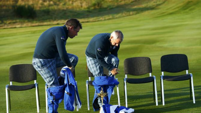 Europe Ryder Cup captain Paul McGinley and Lee Westwood remove wet weather gear ahead of the 2014 Ryder Cup at Gleneagles