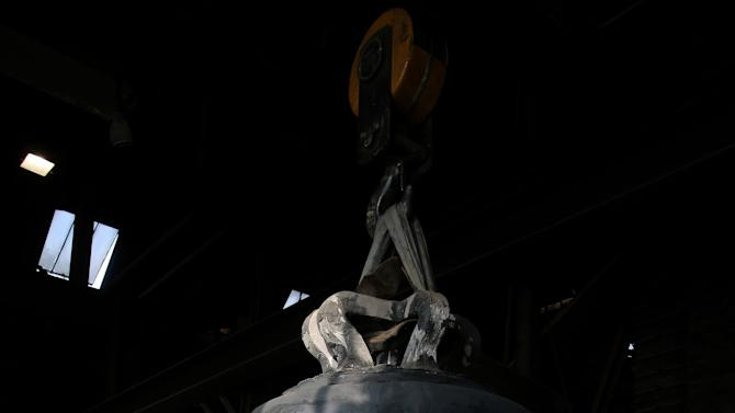 """A founder looks at the new bell bound for Notre Dame cathedral in Paris, """"Gabriel"""" is seen Friday, Dec. 7, 2012, in the foundry of Villedieu les Poeles, Normandy, France.  Paris' Notre Dame Cathedral will be celebrating its 850th anniversary starting Wednesday Dec. 12, 2012,  and Gabriel will join the peal of bells at the medieval landmark cathedral. (AP Photo/David Vincent)"""