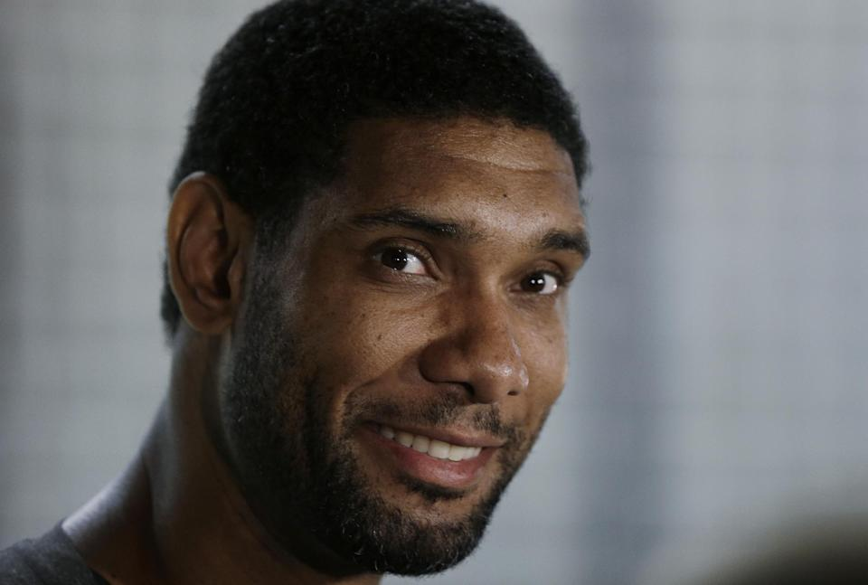 San Antonio Spurs' Tim Duncan, center, talks to reporters at the team's workout facility during their NBA basketball media day, Monday, Sept. 30, 2013, in San Antonio. (AP Photo/Eric Gay)