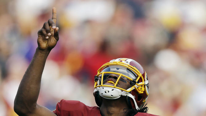 Washington Redskins quarterback Robert Griffin III points toward the sky in celebration after throwing a touchdown pass to wide receiver Aldrick Robinson during the first half of an NFL football game against the Philadelphia Eagles in Landover, Md., Sunday, Nov. 18, 2012. (AP Photo/Patrick Semansky)