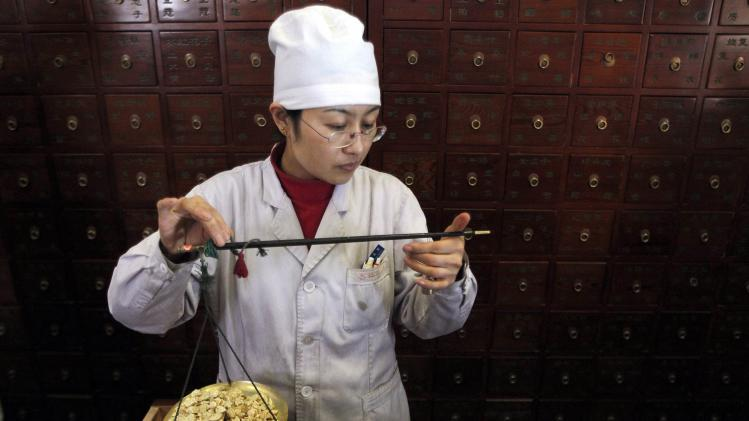 File photo of a worker weighing Chinese herbs as she prepares prescriptions at Beijing's Capital Medical University Traditional Chinese Medicine Hospital