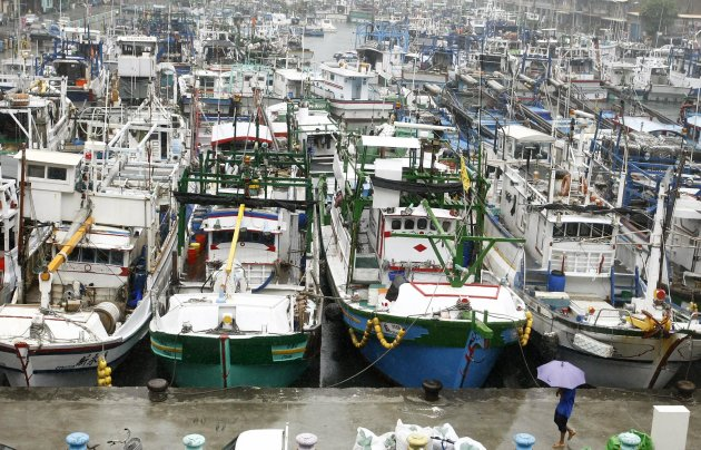 A man walks past boats docked in a harbour as Typhoon Nanmadol approaches the northeastern coastal town of Nanfangao in Ilan county