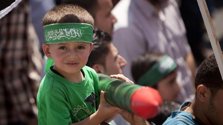 A Palestinian boy, along with supporters of Hamas, holds a representation of a rocket during a demonstration to protest against Israel and to support people in Gaza, in the West Bank city of Ramallah on Friday, Aug. 22, 2014. (AP Photo/Majdi Mohammed)