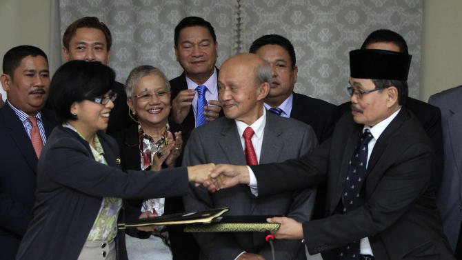 Miriam Coronel-Ferrer, front left, chairperson of Philippine Government Peace Panel, and Mohagher Iqbal, front right, chief negotiator for the Moro National Liberation Front (MNLF), exchange signed documents as Malaysian facilitator Abdul Ghafar Tengku Mohamed, front center, witnesses after the 43rd GPH-MILF Exploratory Talks in Kuala Lumpur, Malaysia, Saturday, Jan. 25, 2014. The Philippine government and the country's largest Muslim rebel group completed talks Saturday on a deal to end four decades of fighting that has killed tens of thousands of people and helped foster Islamic extremism in Southeast Asia. (AP Photo/Lai Seng Sin)