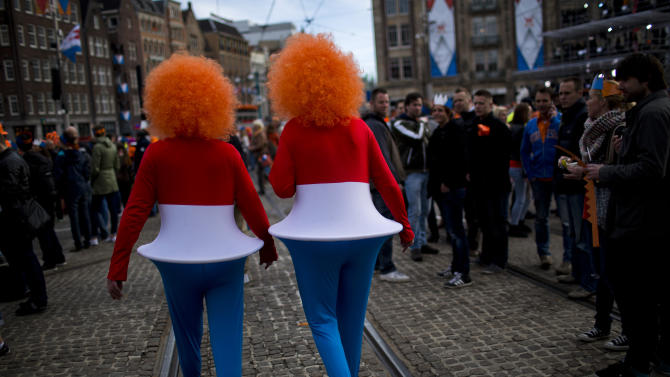 Two men walk in Dam Square as they arrive outside the Royal Palace in downtown Amsterdam, The Netherlands, Tuesday April 30, 2013. Around a million people are expected to descend on the Dutch capital for a huge street party to celebrate the first new Dutch monarch in 33 years. (AP Photo/Emilio Morenatti)