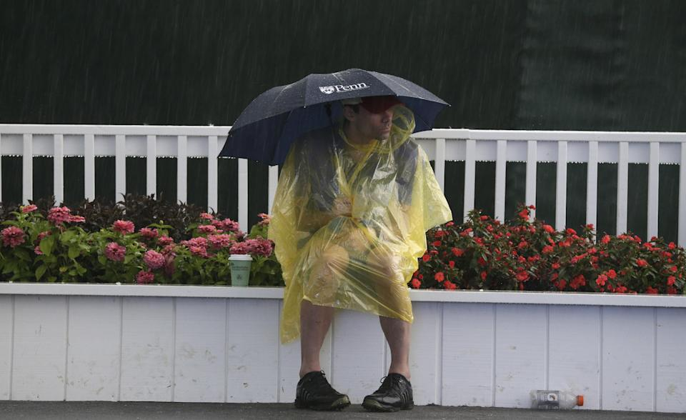A spectator waits out a weather delay during the first round of the U.S. Open golf tournament at Merion Golf Club, Thursday, June 13, 2013, in Ardmore, Pa. (AP Photo/Gene J. Puskar)
