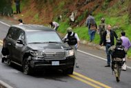 Forensic personnel check a US diplomatic vehicle attacked with gunfire on the Tres Marias-Huitzilac highway in Morelos, Mexico, on August 24. A Mexican judge ordered 12 federal police officers held for 40 days on Monday as prosecutors mull charges against them for shooting at the car and wounding two US government employees. (AFP Photo/Nuvia Reyes)