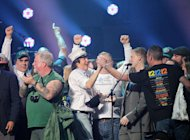 This image released by Starpix shows Paul McCartney, center, on stage with firefighters at the 12-12-12 The Concert for Sandy Relief at Madison Square Garden in New York on Wednesday, Dec. 12, 2012. Proceeds from the show will be distributed through the Robin Hood Foundation. (AP Photo/Starpix, Dave Allocca)