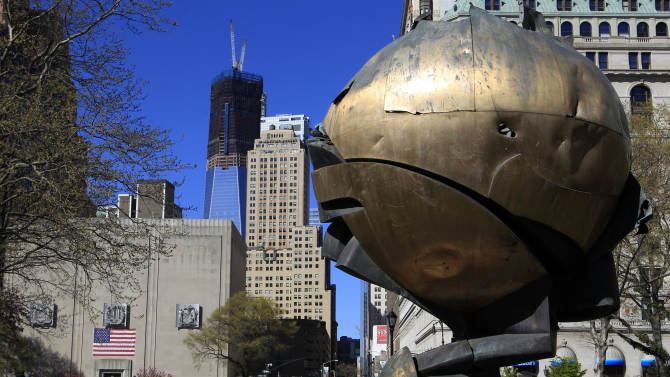 Pedestrians pass 'The Sphere' in Battery Park Friday, April 6, 2012, in New York. The sphere sculpture that emerged largely intact from the rubble of the Sept. 11 attacks, becoming a symbol of resilience and international harmony, will soon be moved from the Manhattan park where it has been on display for a decade. (AP Photo/Frank Franklin II)