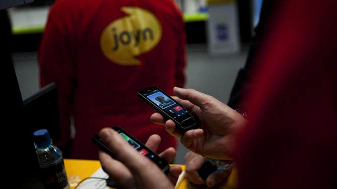 "A worker from Joyn uses a phone to send a message at the world's largest mobile phone trade show in Barcelona, Spain, Thursday March 1, 2012. The new messaging method introduced by the industry group GSMA, or Groupe Speciale Mobile Association, is dubbed ""Joyn"" and will be launched this year by operators in France, Germany, Italy and South Korea. They do it by offering messaging applications that let phone users chat for free on the carriers' data networks or Wi-Fi.  (AP Photo/Emilio Morenatti)"
