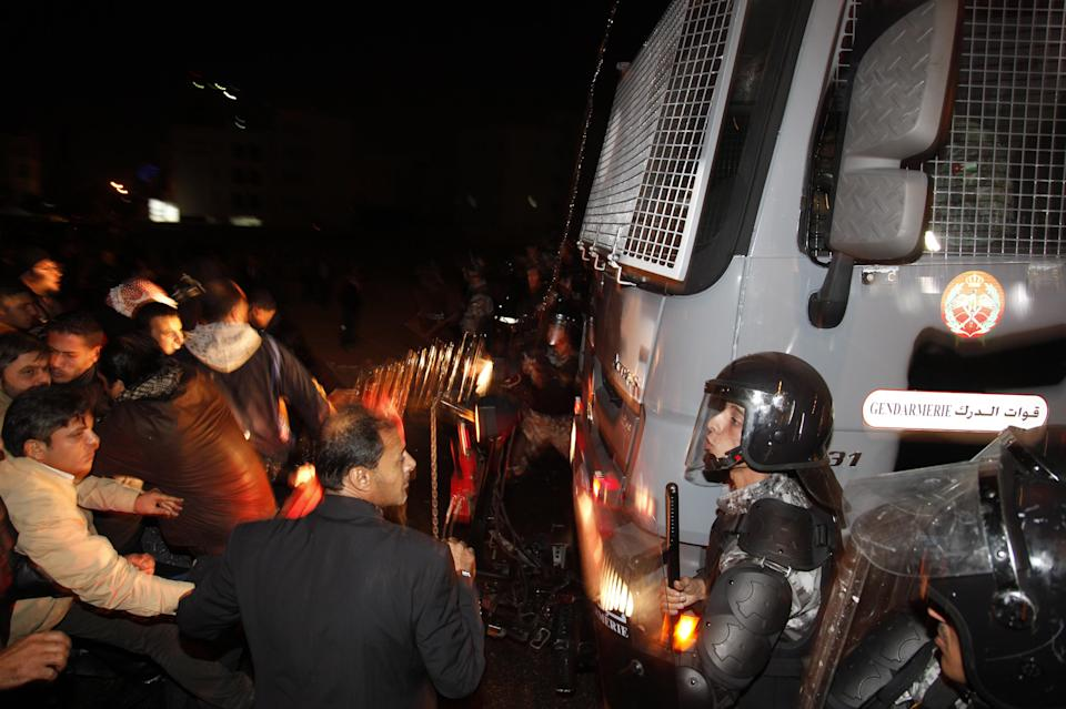 Protesters stand in front of a military truck near the Interior Ministry Circle during a demonstration following an announcement that Jordan would raise fuel prices, including a hike on cooking gas in Amman, Jordan, Wednesday, Nov. 14, 2012. (AP Photo/Mohammad Hannon)