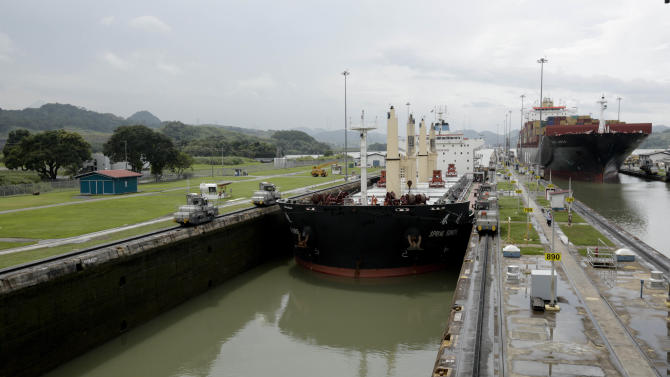In this Aug. 4, 2014, photo, two cargo ships sails though the Miraflores locks on the Panama Canal in Panama City. The Aug. 15 centennial of the opening of the Panama Canal is being marred by increasing doubts about Panama's expansion of the U.S.-built waterway. Disputes between the government and the project's European contractor, as well as labor unions, mean an already-delayed December 2015 completion deadline is unlikely to be met. (AP Photo/Arnulfo Franco)