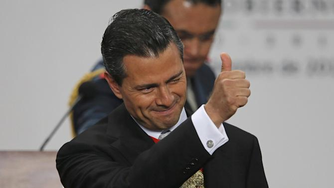 Mexico's President Enrique Pena Nieto gives a thumbs up as he gives his first state-of-the-nation address at Los Pinos presidential residence in Mexico City, Monday, Sept. 2, 2013. Pena Nieto opened his address by praising the passage of a key education reform just hours earlier. (AP Photo/Dario Lopez-Mills)