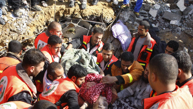 The dead body of a Palestinian woman from the Abdel Aal family is pulled out from the rubble after the family house collapsed during an Israeli forces strike in the Tufah neighbourhood, Gaza City, Sunday, Nov. 18, 2012. The Israeli military widened its range of targets in the Gaza Strip on Sunday to include the media operations of the Palestinian territory's Hamas rulers, sending its aircraft to attack two buildings used by both Hamas and foreign media outlets. (AP Photo/Majed Hamdan)