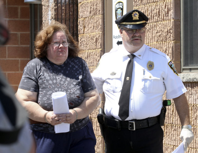 CORRECTS TO CLARIFY CHARGES Susan Gensiak, 59, of Taylor, Pa., is lead by a police officer to arraignment, Wednesday, June 19, 2013 in Scranton, Pa. Gensiak and her two daughters have been charged wit