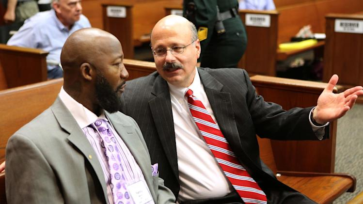 Assistant State Attorney Bernie de la Rionda, right, talks to Tracy Martin, father of slain teen Trayvon Martin, during the George Zimmerman trial in Seminole circuit court in Sanford, Fla., Wednesday, June 12, 2013. Zimmerman has been charged with second-degree murder for the 2012 shooting death of Trayvon Martin.(AP Photo/Orlando Sentinel, Joe Burbank, Pool)