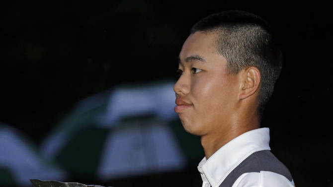 Amateur Guan Tianlang, of China, holds the amateur trophy after the Masters golf tournament Sunday, April 14, 2013, in Augusta, Ga. (AP Photo/Matt Slocum)