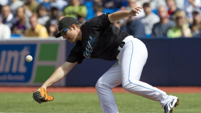 Toronto Blue Jays' Adam Lind fields an errant throw in the first inning of baseball game against the New York Yankees in Toronto, Saturday, Sept. 17, 2011. The Yankees won 7-6. (AP Photo/The Canadian Press, Darren Calabrese)