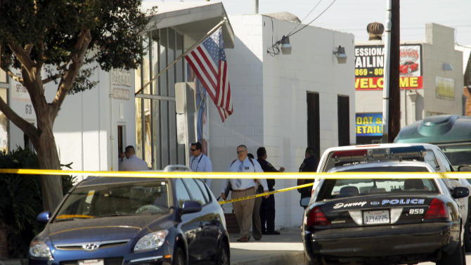 Police investigators stand outside a family-owned business, United States Fire Protection Services, in Downey, Calif., Wednesday, Oct. 24, 2012. Five people were shot and at least two died in shootings at the business and a residence in the Los Angeles suburb Wednesday, according to Downey police Lt. Dean Milligan. The shootings occurred shortly after 11 a.m. at a business and at a nearby home, where family members of the business owner live. A woman was found dead at the home, he said. (AP Photo/Nick Ut)