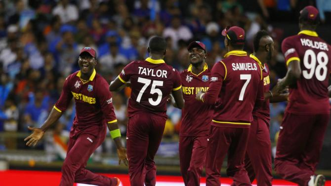 West Indies players celebrate after India's Rohit Sharma was caught by their wicketkeeper Denesh Ramdin off the bowling of Jerome Taylor during their Cricket World Cup match in Perth