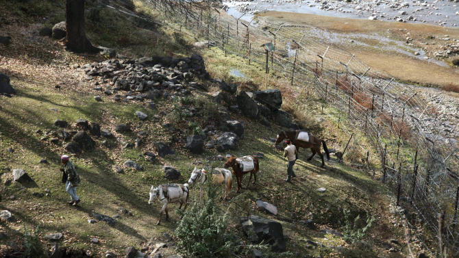 Indian men along with their horses cross near the border village of Dallan, in Poonch, 250 kilometers (155 miles) northwest of Jammu, India, Tuesday, Jan. 15, 2013. India's army chief Gen. Bikram Singh on Monday accused Pakistan of planning an attack in which two Indian soldiers were killed in the disputed Kashmir region last week, and warned of possible retaliation. (AP Photo/Channi Anand)