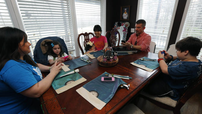 "In this April 4, 2013 photograph, Phillip Smith, right, and wife Niki, left,  are using Google Translate on their iPhones to ""speak"" with their new daughter, 14-year-old Guan Ya, third from right, in their Rienzi, Miss., home. The Smiths and their three other children, Colton, 10, right, GiGi, 3, third from left, and Macy Jade, 7, second from left,  are using the program to communicate almost exclusively with Guan Ya, who is deaf. The family uses iPhones, iPods and a laptop, all loaded with the program to write in English that translates to Chinese and Guan Ya responds with Chinese to English. (AP Photo/Rogelio V. Solis)"