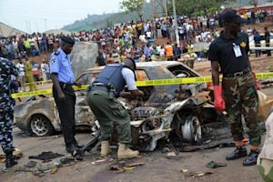 Nigerian security personnel inspect the site of a blast …