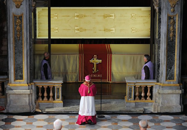 "Archbishop of Turin Cesare Nosiglia, center, kneels in front of the Shroud of Turin that went on display for a special TV appearance Saturday, March 30, 2013. The Shroud went on display amid new research disputing claims it's a medieval fake and purporting to date the linen some say was Jesus' burial cloth to around the time of his death. Pope Francis sent a special video message to the event in Turin's cathedral, but made no claim that the image on the shroud of a man with wounds similar to those suffered by Christ was really that of Jesus. He called the cloth an ""icon,"" not a relic — an important distinction. ""This image, impressed upon the cloth, speaks to our heart and moves us to climb the hill of Calvary, to look upon the wood of the Cross, and to immerse ourselves in the eloquent silence of love,"" he said. (AP Photo/Alessandro Di Marco, Pool)"