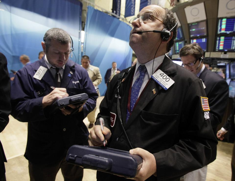Gordon Charlop, center, works with fellow traders on the floor of the New York Stock Exchange Wednesday, Aug. 10, 2011. (AP Photo/Richard Drew)