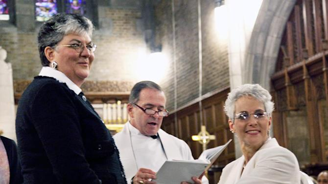 In this photo provided by Outserve-SLDN, Brenda Sue Fulton, left, and Penelope Gnesin, hold hands while exchanging wedding vows at the U.S. Military Academy at West Point, N.Y.  Saturday, Dec. 1, 2012. Their ceremony marks the first time a same sex couple had their wedding in the Cadet Chapel, the landmark gothic church that is a center for spiritual life at the Academy. (AP Photo/Outserve-SLDN, Jeff Sheng)