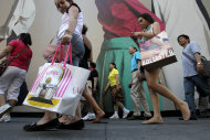 FILE - In this July 5, 2011 file photo, dedestrians with shopping bags make their way along Fifth Avenue in New York. The U.S. economy grew more slowly in the summer than previously thought because consumers spent less than the government had first estimated. But economists expect growth in the current October-December quarter to be stronger. (AP Photo/Seth Wenig, File)