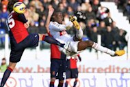 AC Milan&#39;s forward Mario Balotelli (R) kicks the ball past Cagliari&#39;s defender Luca Rossettini (L) during their Italian Serie A football match at Cagliari&#39;s Is Arenas stadium on February 10, 2013. The match ended in a 1-1 draw