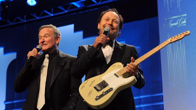 """COMMERCIAL IMAGE - Robin Williams, left, and Billy Crystal auction off a guitar autographed by Glenn Frey, of the Eagles, at the 12th Annual Starkey Hearing Foundation """"So The World May Hear"""" Gala on Saturday, Aug. 4, 2012 in St. Paul, Minn. The foundation conducts dozens of hearing missions every year in the U.S. and around the world and has given the gift of hearing in more than 97 countries. (Photo by Diane Bondareff/Invision for Starkey Hearing Foundation/AP Images)"""