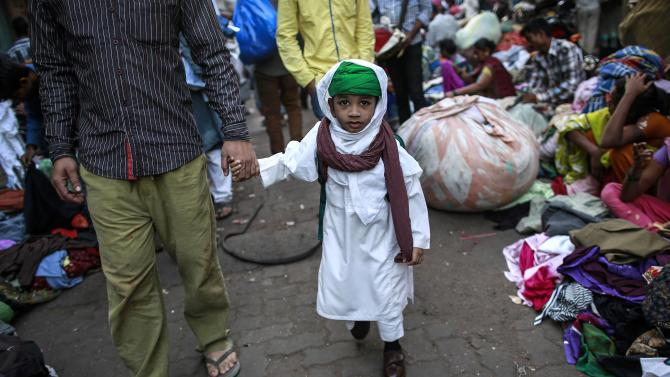A boy walks with his father to school through a second-hand street side clothing market in Mumbai