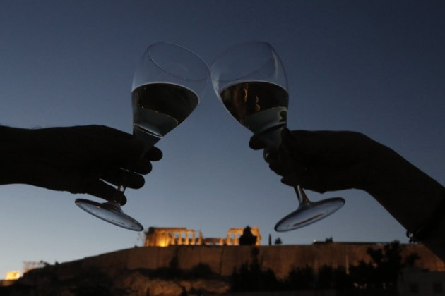 Couple clinks glasses as they pose for a photograph with the temple of the Partenon in the background at the Athens Acropolis Museum