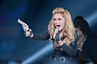 US pop-star Madonna performs during her current world tour on July 7. France&#39;s far-right National Front says it plans to sue Madonna over a video at the US pop star&#39;s concert in France showing party leader Marine Le Pen with a swastika on her forehead