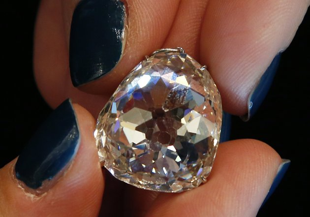An employee holds a 400-year-old and 34.98 carats diamond known as