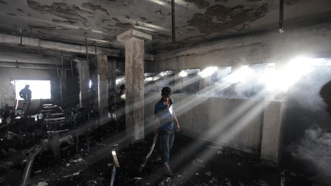 Bangladeshi workers inspect the damage inside a two-storied garment factory that caught fire in Dhaka, Bangladesh, Saturday, Jan.26, 2013. The fire killed at least six female workers and injured another five,  police and fire officials said. The latest fire occurred more than two months after a deadly fire killed 112 workers in another factory near the capital city, raising questions about the safety measures in Bangladesh garment industry. (AP Photo/A.M. Ahad)