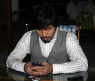 Philippine boxing superstar Manny Pacquiao browses his cellular telephone at his house in General Santos City, in southern island of Mindanao. Pacquiao filed a defamation lawsuit against US boxer Floyd Mayweather, saying there is sufficient evidence of malicious acts in accusing Pacquiao of being a dope cheat