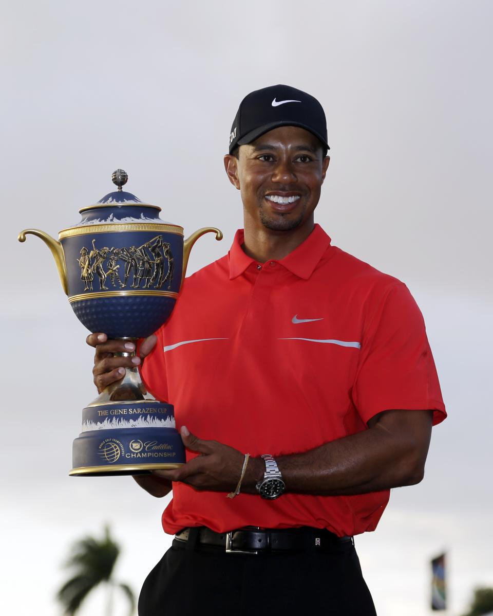 Tiger Woods holds the Gene Sarazen Cup for winning the Cadillac Championship golf tournament on Sunday, March 10, 2013, in Doral, Fla. (AP Photo/Wilfredo Lee)