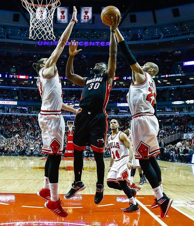 THM20. Chicago (United States), 09/03/2014.- Miami Heat guard Norris Cole (C) shoots between Chicago Bulls center Joakim Noah (L) and Chicago Bulls forward Taj Gibson (R) in the second half of their N